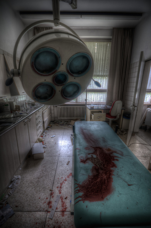 Operation room in abandoned hospital in east Germany with lights and blood covered bench