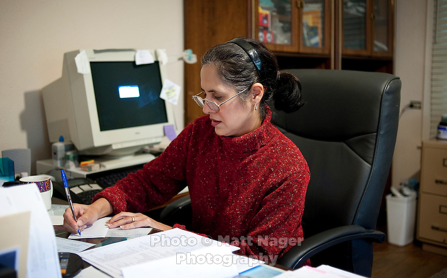 Martha Woodard (cq), at her home office in Laredo, Texas, US, Thursday, Dec. 10, 2009. Martha and her husband John Woodard were forced to move their office from the apartment complex they own and manage, to their home in order to rent out the original space to make more money. Because of the slumping economy, John is looking into getting another job to make ends meet. Martha, a native Spanish speaker from Mexico, is learning English, in part, to help take over managing their apartment business and be able to answer phone calls in English. ..PHOTOS/ MATT NAGER