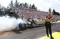 Aug. 2, 2014; Kent, WA, USA; Crew chief Todd Smith plugs his ears as NHRA top fuel dragster driver Brittany Force does her burnout during qualifying for the Northwest Nationals at Pacific Raceways. Mandatory Credit: Mark J. Rebilas-