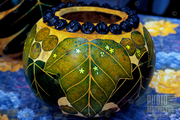 A nature-decorated Hawaiian gourd ringed with kukui nuts for sale at a Kapiolani Park craft market