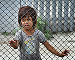 A girl looks through a fence in a largely Roma, Turkish-speaking neighborhood of Dobrich, in the northeast of Bulgaria.