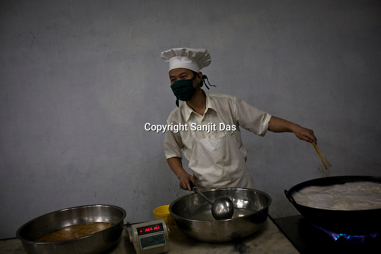 A Chinese chef prepares noodles for breakfast at the dining hall of the Chinese colony of Adani Power plant in Mundra port industrial city of Gujarat, India. Indian power companies have handed out dozens of major contracts to Chinese firms since 2008. Adani Power Ltd have built elaborate Chinatowns to accommodate Chinese workers, complete with Chinese chefs, ping pong tables and Chinese television. Chinese companies now supply equipment for about 25% of the 80,000 megawatts in new capacity.