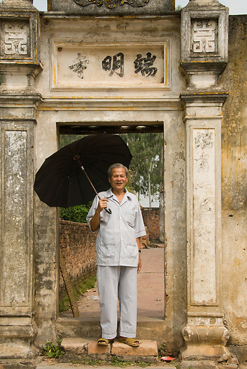 Mr Cung, the head man in the small village of Tho Ha proudly stands outside of the oldest communal house and pagoda in North Vietnam.  ..