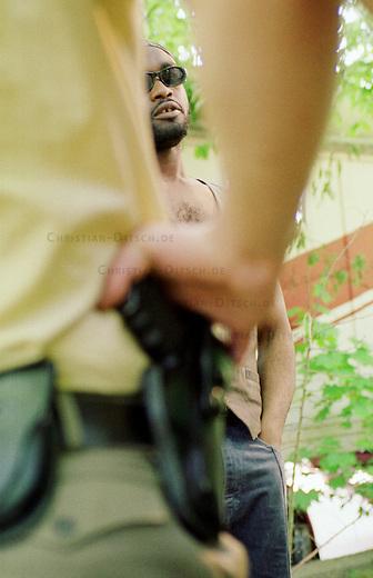 Polizeikontrolle eines Mannes aus Ghana in der Hasenheide, einer Parkanlage im Berliner Bezirk Neukoelln. Nach Polizeiaussagen sollen in der Parkanlage Maenner aus Afrika Drogen verkaufen.<br /> Der hier festgehaltene Mann wurde nach Angaben des Einsatzleiters den ganzen Tag lang beobachtet. Diese Aussage war nachweislich falsch. Der Mann, ein Rechtsanwalt, hat sich extra fuer diese Fotos sog. &quot;szenetypische Kleidung&quot; besorgt und angezogen und sich als Testperson fuer einen Artikel zum Thema Kontrollen von Auslaendern in diese Situation begeben.<br /> 4.5.2000, Berlin<br /> Copyright: Christian-Ditsch.de<br /> [Inhaltsveraendernde Manipulation des Fotos nur nach ausdruecklicher Genehmigung des Fotografen. Vereinbarungen ueber Abtretung von Persoenlichkeitsrechten/Model Release der abgebildeten Person/Personen liegen nicht vor. NO MODEL RELEASE! Nur fuer Redaktionelle Zwecke. Don't publish without copyright Christian-Ditsch.de, Veroeffentlichung nur mit Fotografennennung, sowie gegen Honorar, MwSt. und Beleg. Konto: I N G - D i B a, IBAN DE58500105175400192269, BIC INGDDEFFXXX, Kontakt: post@christian-ditsch.de<br /> Bei der Bearbeitung der Dateiinformationen darf die Urheberkennzeichnung in den EXIF- und  IPTC-Daten nicht entfernt werden, diese sind in digitalen Medien nach &sect;95c UrhG rechtlich gesch&uuml;tzt. Der Urhebervermerk wird gemaess &sect;13 UrhG verlangt.]