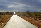 Near Bujumbura, Tanzania. Lorry on straight new tarmac road through savannah landscape.