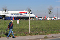 BNPS.co.uk (01202 558833)<br /> Pic: CorinMesser/BNPS<br /> <br /> A walker strolls past the plane flleet.  <br /> <br /> Fleet of BA planes still arriving at Bournemouth Airport today (Thursday)<br /> <br /> Bournemouth Airport has today been turned into a plane park for British Airways aircraft that have nowhere else to go during the coronavirus pandemic.<br /> <br /> More than 30 BA aircraft are expected to arrive in Dorset following the collapse of global air travel.<br /> <br /> Major airports like Heathrow and Gatwick are already full with grounded planes.<br /> <br /> With no room left to park them BA is having to fly its A320 planes to regional airports like to Bournemouth.