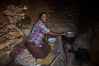 Uganda, Wamala. Mayi Nankya using her a BioLite wood cook stove at home.