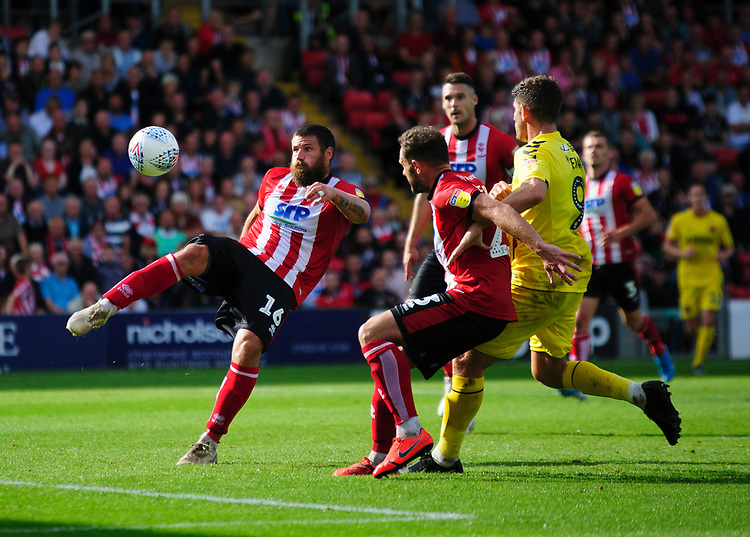 Lincoln City's Michael Bostwick clears under pressure from Fleetwood Town's Ched Evans<br /> <br /> Photographer Andrew Vaughan/CameraSport<br /> <br /> The EFL Sky Bet League One - Lincoln City v Fleetwood Town - Saturday 31st August 2019 - Sincil Bank - Lincoln<br /> <br /> World Copyright © 2019 CameraSport. All rights reserved. 43 Linden Ave. Countesthorpe. Leicester. England. LE8 5PG - Tel: +44 (0) 116 277 4147 - admin@camerasport.com - www.camerasport.com