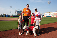 "Springfield Cardinals General Manager Matt Gifford stands with his family and dog on the field prior to a game between the Arkansas Travelers and the Springfield Cardinals at Hammons Field on May 5, 2012 in Springfield, Missouri. Saturday's game was called ""A Bark in the Park"" Night, and fans could bring their dogs to Hammons Field with them. (David Welker/Four Seam Images)."