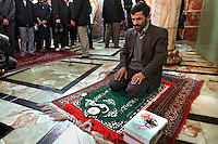 Iranian President Mahmoud Ahmadinejad sits kneeled saying the morning prayer in the holy city of Qom prior to a speech he is going to give to a crowd of locals.