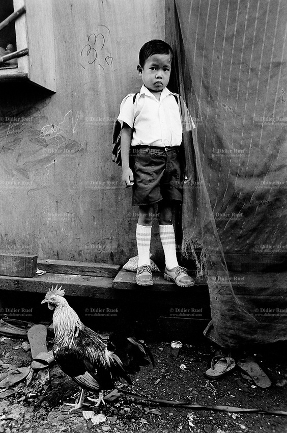 Philippines. Luzon Region. Manila. Tondo area. Smokey mountain is a rubbish dump. Life on a garbage heap. Young boy on his way to school carries a backpack. The kid is wearing the school uniform. Clean clothes, tight shoes, socks, a pair of shorts and a white shirt. He is also well combed. Cock. © 1992 Didier Ruef .