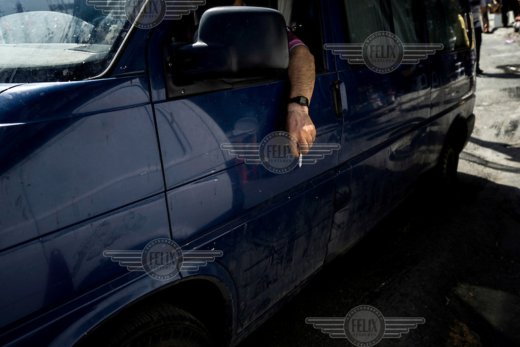 A man in a van holds a cigarette out of the driver's side window.