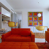 The open-plan living/dining area is furnished with brightly coloured modern furniture