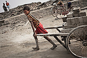A young boy from the Chowduli class pulls a cart of unbaked bricks at a local brick kiln in Abadmanpur village of North 24 Parganas in West Bengal, India. Photo: Sanjit Das/Panos for The Wall Street Journal. Slug: ICASTE
