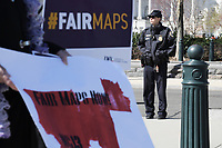 Washington, DC - March 26, 2019: A Supreme Court police officer stands outside the Court building in Washington, DC March 26, 2019, as protesters holds signs about gerrymandering.  (Photo by Lenin Nolly/Media Images International)