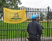 """United States Park Police officer look away from a flag erected on the White House fence by members of the """"Million Veterans March on the Memorials"""".  The protest concerns the closing of the memorials on the National Mall due to the partial shut-down of the government on Pennsylvania Avenue near the White House in Washington, D.C. on Sunday, October 13, 2013.<br /> Credit: Ron Sachs / CNP"""