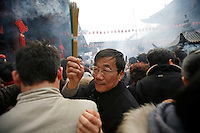 A man squeezes through the crowd while holding high his incense sticks at the Jade Buddha Temple in Shanghai, China. The first day of the Chinese New Year is one of the most auspicious days in the year to offer incense and prayers..18 Feb 2007