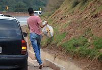 BRUMADINHO MG, 25 Julho 2013 - Um acidente com um caminhao carregado com cestas basicas que ia de BH a Pouso Alegre MG e perdeu o freio no trajeto, interrompu uma faixa da Rodovia Fernao Dias na altura do KM 526 na região de Brumadinho, MG nesta quinta  feira, 25.   na foto Populares fogem com cestas basicas(FOTO: ALAN MORICI / BRAZIL PHOTO PRESS).