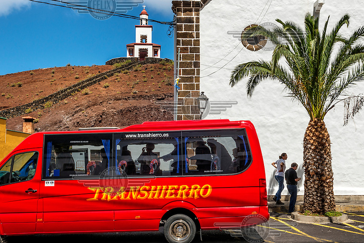 A bright red mini bus disgorges tourists near a church and an exotic palm. /Felix Features