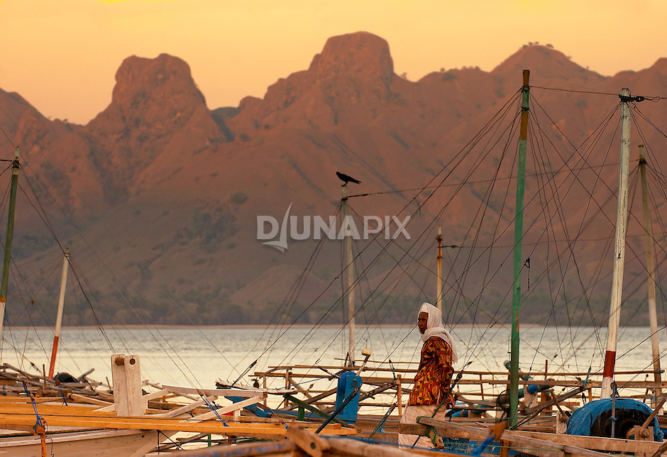 Sunrise on boat, mountains, olm man and crow, Komodo Village, Komodo National Park