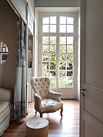 A view into a bedroom decorated in shades of grey. A full height pair of french doors allows plenty of light into the room. An upholstered armchair is set next to a bed recess.