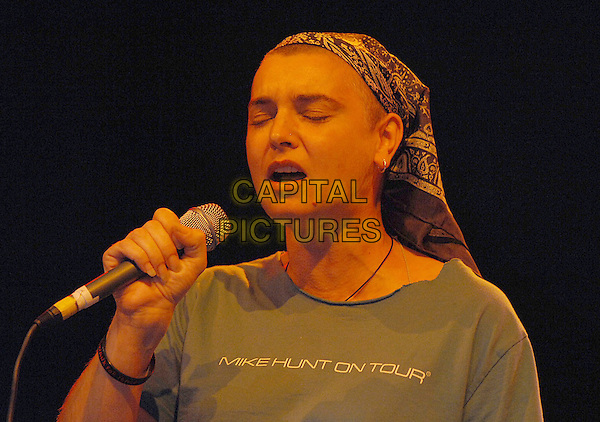 "SINEAD O'CONNOR.Performs live at the V Festival 2007, Hylands Park, Chelmsford, Essex, England. .August 18th 2007.headshot portrait funny t-shirt blue slogan ""Mike Hunt On Tour"" headscarf scarf head on stage gig concert performance music microphone mouth open.CAP/BEL.©Belcher/Capital Pictures"