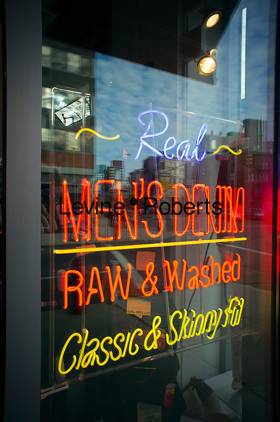 A store in New York advertises its denim with a neon sign in the window, seen on Saturday, January 28, 2012.  (© Richard B. Levine)