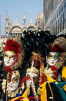 Person surrounded by elaborate masks for sale on St Mark's Basilica, Venice, Italy.