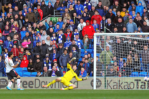 22.03.2014  Cardiff, Wales. Luis Suárez of Liverpool scores his hat trick, third goal past goalkeeper Marshall during the Premier League game between Cardiff City and Liverpool from Cardiff City Stadium.
