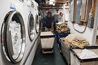 Allan Baxter, 40, works in the laundry of the Harborside Inn in Edgartown, Martha's Vineyard, Massachusetts, USA, on Tues., July 25, 2017.  From St. Mary Parish, Jamaica, Baxter has worked at the hotel on an H2B visa for seasonal foreign workers. He spent last winter working in Stowe, Vermont, as well. The hotel has had difficulty this year getting as many H2B visas as it had in previous years. As a result, Baxter is the only person working in the laundry room on most days; it was a two-person job last year. Workers from other areas of the hotel sometimes work short shifts in the laundry room to help Baxter.