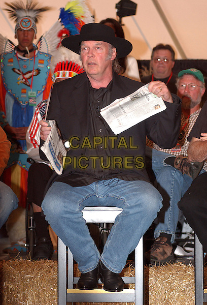 NEIL YOUNG.20th Anniversary FARM AID 2005 Press Conference held at the Tweeter Center, Tinley Park, IL, USA. .September 18th, 2005.Photo Credit: Jason L Nelson/AdMedia/Capital Pictures.Ref: JN/ADM/CAP .full length black jacket hat jeans denim sitting newspapers.www.capitalpictures.com.sales@capitalpictures.com.© Capital Pictures.