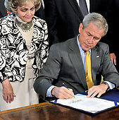 Washington, D.C. - July 29, 2008 -- United States President George W. Bush signs H.J. Resolution 93, the Renewal of Impoet Restrictions on Burma and H.R. 3890, the Tom Lantos Block Burmese JADE (Junta's Anti-Democratic Efforts) Act of 2008 in the Oval Office of the White house in Washington, D.C. on Tuesday, July 29, 2008.  Annette Lantos, wife of the late US Representative Tom Lantos (Democrat of California), looks on from left.<br /> Credit: Ron Sachs / Pool via CNP
