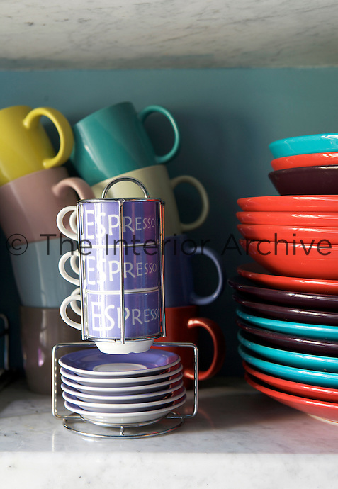 A colourful collection of mugs, plates and espresso cups and saucers on a marble shelf in the kitchen