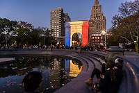 New York, NY - 15 November 2015 NYC  The arch in Washington Square Park lights up in solidarity with Paris.  Beneath the arch is a candlelight shrineto commemorate the victims of the 13 November Paris terror attacks.