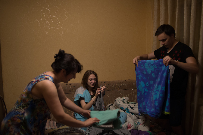 Katrine, her mother and ALexander folding loundery.