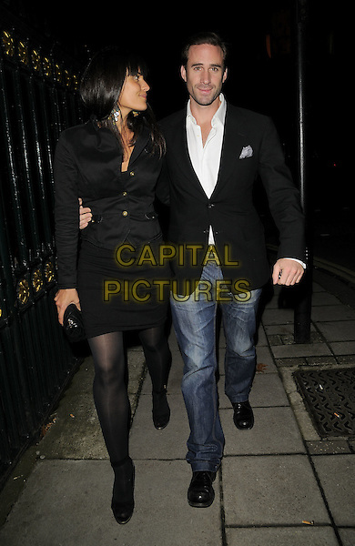 MARIA DOLORES & JOSEPH FIENNES.The Vivienne Westwood & London Musici concert & catwalk show, Chaos Point, in aid of NSPCC, Banqueting House, Whitehall, London, England..November 18th, 2008.full length black jacket dress jeans denim couple clutch bag profile.CAP/CAN.©Can Nguyen/Capital Pictures.