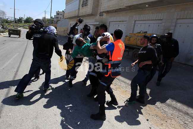 Palestinians carry an injured protesters during clashes with Israeli soldiers at a protest calling for the release of Palestinian prisoners held in Israeli jails, outside Israel's Ofer military prison near the West Bank city of Ramallah April 4, 2014. Israel has called off a planned release of Palestinian prisoners meant to advance the U.S.-sponsored peace process and called for a review of how the troubled negotiations can make progress, an official briefed on the talks said on Thursday. Photo by Issam Rimawi