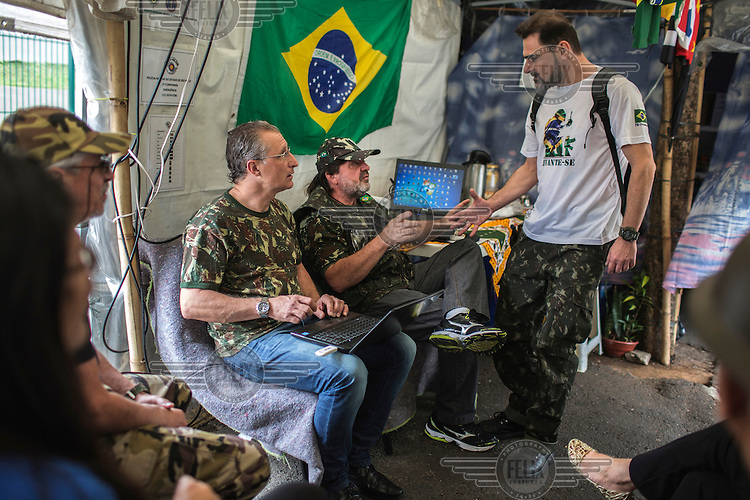 National Guards member Adans Ghizzi, of Campinas, (centre right), with Sergio Veber, 51, (centre left) and Reinaldo Bueno, 46, (right) of the Brazilian Interventionist Resistence Movement (MBRI) at their headquarters, called PR 1 - Sergeant Mario Kozel Filho Military Interventionist Camp, a radical group that wants military intervention in the government. <br /> <br /> Their headquarters is a makeshift tarpaulin camp situated on an island in the middle of Sergeant Mario Kozel Filho Avenue, between the State Legislative Assembly and the Ministry of the Military.