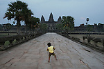 CAMBODIA  -  APRIL 7, 2005:  A young boy dances on a pathway leading to Angkor Wat at dusk in Siem Reap on April 7th, 2005 in Cambodia.  (PHOTOGRAPH BY MICHAEL NAGLE)