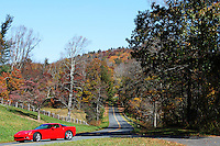 Stock photo - Gorgeous red car passing by on a sloped road on Blue Ridge Parkway, North Carolina, America.