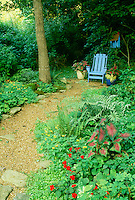 A peaceful place to sit: Blue painted adirondack chair with matching whimsical birdhouse are the destination on a garden path