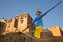 Rajasthani girl performing balancing act on high rope near entrance gate of Jaisalmer Fort, Jaisalmer, Rajasthan, India --- Model Released