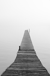 A dock leads into th light of a foggy morning on the St. John's River.
