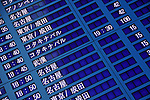 Airport display board with Japanese characters and flight times.