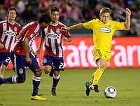 Columbus Crew midfielder Robbie Rogers (18) moves past Chivas USA midfielder Paulo Nagamura (26) and Dario Delgado (12). CD Chivas USA defeated the Columbus Crew 3-1 at Home Depot Center stadium in Carson, California on Saturday July 31, 2010.