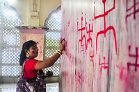 "TRIPURA, INDIA - JUNE 22: A woman draws a Holy Signs known as ""swastik"", wishing happy married life on the occasion of Ambubachi in a local temple on June 22, 2017 in Tripura, India. Ambubachi is the celebration of the menstruation of mother earth. The believe is, During Ambubachi , for three days mother earth herself menstruates. (Photo by Abhisek Saha/VIEWpress via Getty Images)"