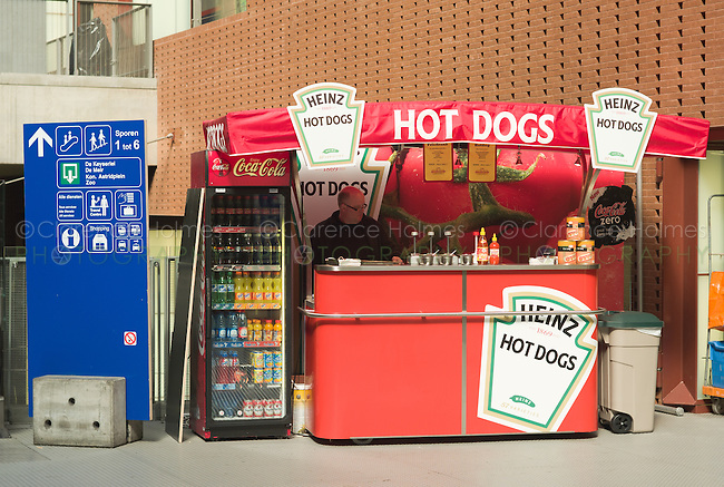 A man sells food and soft drink at a hot dog stand located in Antwerp Central Station