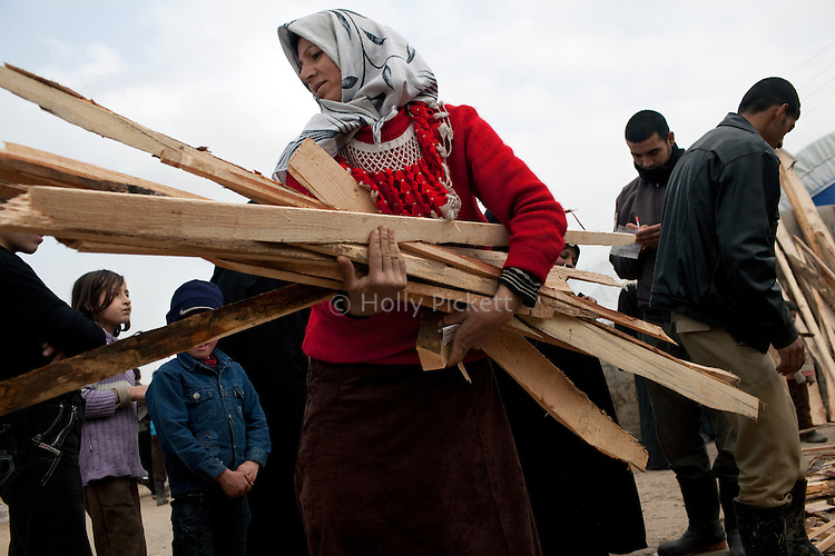A Syrian woman carries wood for heating her tent at Azaz Camp, just inside the Syrian border with Turkey, Feb. 23, 2013. According to administrators, this camp holds roughly 9,000 to 10,000 internally displaced persons (IDP's). Two meals per day are provided by a Turkish humanitarian organization, and Qatar Red Crescent provided tents. There is very little electricity, and no running water. There is also a refugee camp on the Turkish side of the border, but it is full. The UN Refugee Agency has reported a sharp increase in refugees fleeing Syria for neighboring countries in the first months of 2013.