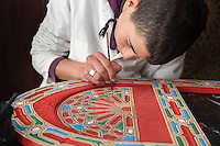 A boy painting his geometric design in a lesson in painted woodwork at the Artisan School or Dar Sanaa, founded 1919 under the Spanish Protectorate of Morocco, which teaches the traditional art and craft skills of woodwork, zellige, sculpted plaster, leatherwork, etc, in Tetouan on the slopes of Jbel Dersa in the Rif Mountains of Northern Morocco. Tetouan was of particular importance in the Islamic period from the 8th century, when it served as the main point of contact between Morocco and Andalusia. After the Reconquest, the town was rebuilt by Andalusian refugees who had been expelled by the Spanish. Picture by Manuel Cohen