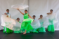 Girls wearing green dresses dancing Chinese Moon Fan Dance, Northwest Folklife Festival 2016, Seattle Center, Washington, USA.